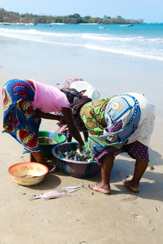 Working together in silence the women sort the daily catch.