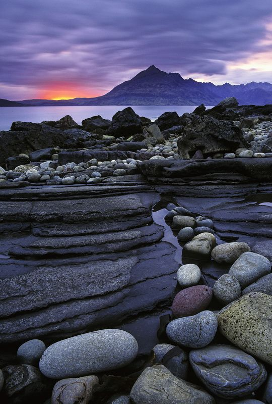 Elgol is always a highly productive place for pictures it is a fabulous beach but the backdrop is even more remarkable with the toothy grimace of the Cuillin ridge beyond the sea loch. I got in close and low to a string of coloured stones that naturally curved towards the ridge of mountains and waited for a show of colour in the sky. for a few seconds therewas a crimson smear of unbelievable intensity and depth that fought its way through the clouds.