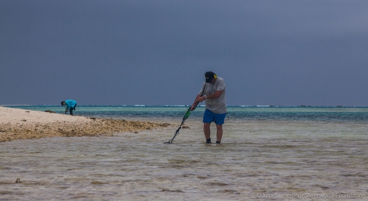 Silentworld Foundation CEO and project team leader John Mullen uses a metal detector to search for artefacts in shallows off Observatory Cay, while Jacqui Mullen (background) documents a find. Image: Julia Sumerling/Silentworld Foundation.